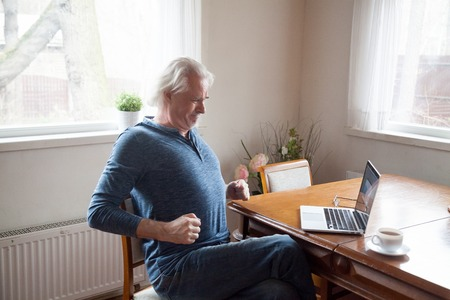 Grey haired middle aged senior male sitting alone in the kitchen on chair stretching back after long time working on computer doing exercises for loins preventing osteoarthritis and spinal stenosis. Stock fotó