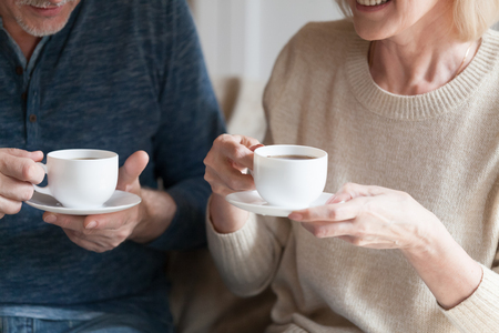 Positive middle aged spouses sitting at home holding cups with black tea beverage. Mature senior wife and husband spending time together drinking afternoon coffee and chatting, close up cropped image 写真素材