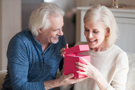 Spouses celebrating special occasion, grey haired husband giving to loving pretty happy wife pink gift box with long awaited present, she feels excited and satisfied. Making joy to loved ones concept Stockfoto