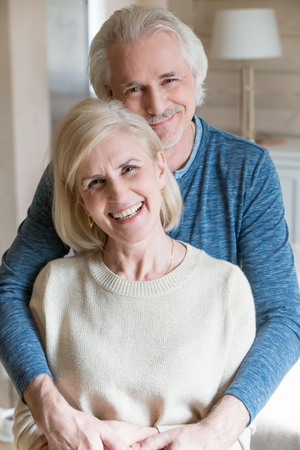 Vertical image of middle aged attractive grey haired couple in love standing in living room laughing posing for camera. Wellbeing healthy cheerful positive spouses in casual clothes shooting at home