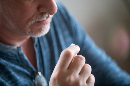 Close up mature man holds pill on hand. Health problem including diseases of cardiovascular, erectile dysfunction and tablets reducing high cholesterol level supplements for men over 50 years concept