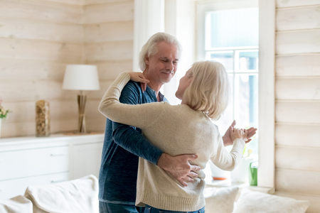 Happy middle aged spouses in casual clothes celebrating long lasting living together anniversary standing in cozy light living room, loving grey haired husband embracing beloved wife and dancing tango Фото со стока