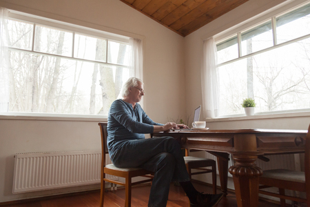 Senior man sitting on chair in spacious room at table working on pc typing article working on internet magazine having hobby earns money online. Retired person living full life using modern technology