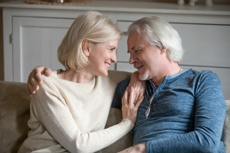 Happy cheerful senior retired couple sitting on sofa in cozy living room, loving husband embrace beloved wife, aged people chatting enjoying time together at home feeling comfort and positive emotions Stock Photo