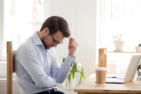 Gefrustreerde depressieve man die zich een verliezer voelt die in de buurt van een laptop zit, geschokt door faillissement, bedrijfsfalen, gestrest vermoeide zakenman wanhopig bezorgd over verloren geld online schuldenprobleem, slecht nieuws, fiasco