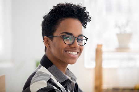 Headshot of happy african american girl looking at camera, black woman posing indoors smiling, mixed race female pretty student, millennial businesswoman, young professional wearing glasses portrait