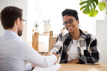 Gelukkig zelfverzekerde Afrikaanse sollicitant die hand schudt van hr-manager biedt nieuwe baan aan, zwarte kandidaat wordt aangenomen bij sollicitatiegesprek, handdrukklant tijdens vergadering, maakt goede eerste indruk werkgelegenheidsconcept