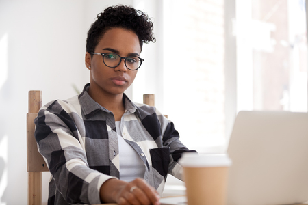 Pensive thoughtful african american woman thinking of problem solution at work with laptop, serious millennial black girl searching new ideas lost in thoughts in office feeling upset or reflecting