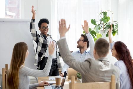 Diverse zakenmensengroep steekt de hand op bij bedrijfspresentatietraining, gelukkig multi-etnisch medewerkersteam neemt deel aan stemvrijwilligerswerk, stelt vragen op conferentie met afrikaanse coachleider