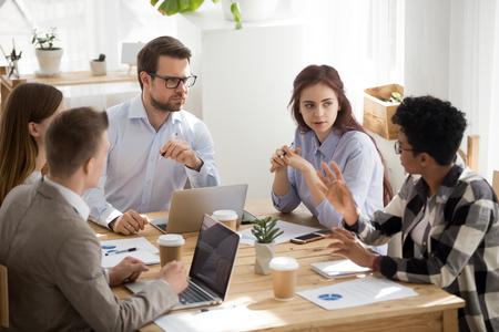Sceptische blanke collega's luisteren naar Afrikaanse werknemer-stagiair die mening slecht idee geeft tijdens groepsbijeenkomst, incompetente zwarte werknemer die spreekt op diverse briefing, rassendiscriminatie op het werkconcept Stockfoto