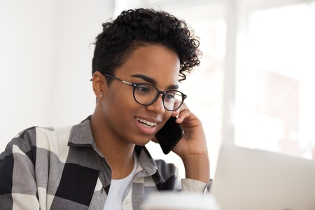 Happy black female saleswoman talking on the phone, friendly african american woman entrepreneur making call having conversation giving customer service support speaking by cellphone