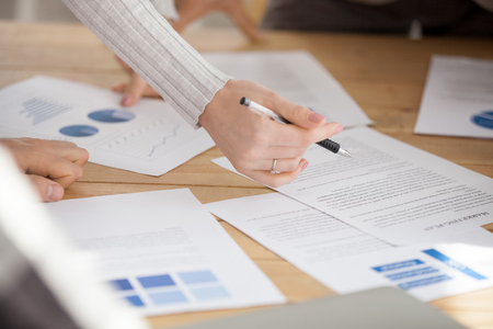 Business people working with papers brainstorming new marketing plan at office desk, designers analyze statistics report paperwork documents on table project team cooperate, teamwork, close up view