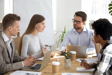 Różnorodni koledzy słuchają, jak współpracownik rozmawia o nowym biznesplanie na spotkaniu grupowym, wieloetniczni pracownicy przeprowadzają burzę mózgów na temat projektu, dzielą się kreatywnymi pomysłami na odprawie korporacyjnej, koncepcji dyskusji zespołowej