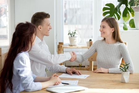 Smiling friendly hr manager handshake applicant welcoming at job interview or hiring successful candidate, satisfied recruiter female seeker shaking hands at meeting, recruitment employment concept Stock Photo