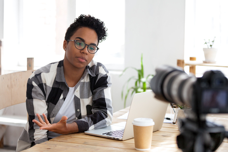 Serious african girl blogger vlogger talking to camera shooting educational video filming webinar blog, black female business coach teacher speaking recording vlog training or job interview