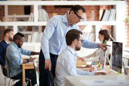 Gerente corporativo ejecutivo que ayuda a un colega masculino con la tarea de la computadora en la oficina, mentor hablando supervisando la formación de la enseñanza compañero de trabajo en prácticas explicando el trabajo en línea apuntando en la PC en el lugar de trabajo Foto de archivo