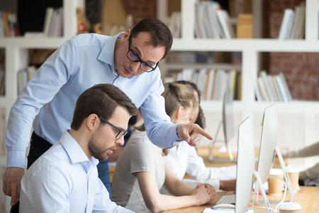 Wütender Chef, der schimpft, traurigen männlichen Mitarbeiter wegen Computerfehler-Inkompetenz am Arbeitsplatz zu schimpfen, verrückter Führer, der zurechtgewiesen hat, schreit untergeordneten faulen Arbeiter an und beschuldigt schlechte Arbeit im Büro