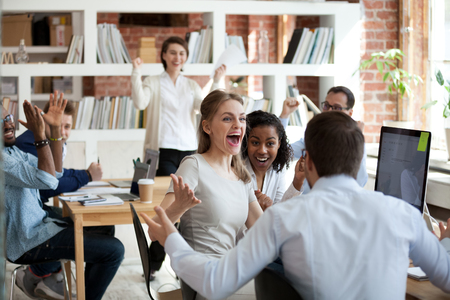 Excited diverse business team employees screaming celebrating good news business win corporate success, happy multi-ethnic colleagues workers group feeling motivated ecstatic about great achievement Stock Photo