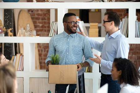 Friendly executive manager ceo welcoming happy african american employee greeting new hired worker in office on first day of work, boss introducing black intern get acquainted with corporate team