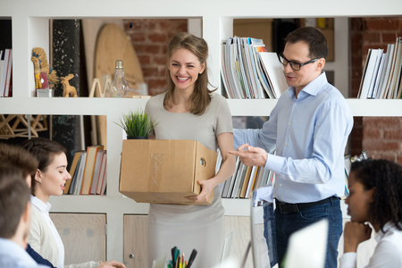 Excited new employee holding box get acquainted with team on first day concept, friendly executive ceo introducing welcoming female intern newcomer supporting hired corporate worker starting work