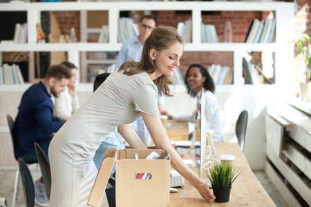 Happy businesswoman new employee unpacking box with personal belongings in office, smiling female hired worker newcomer intern unbox stuff at workplace desk got new job on first day at work concept Stock Photo - 116533563