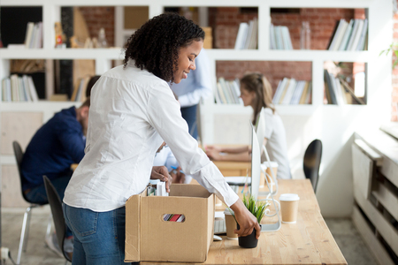 Happy young black newcomer newbie unpacking box with belongings at workplace on first working day concept, smiling african american new hired worker employee intern settling on work desk in office