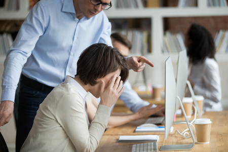 Stressed employee intern suffering from gender discrimination or unfair criticism of angry male boss shouting scolding firing female worker for bad work, computer mistake or incompetence in office 免版税图像