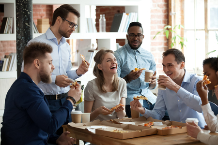 Happy diverse team people talking laughing at funny joke eating ordered pizza in office, friendly employees group enjoy positive emotions sharing lunch together having fun at work break on friday Stock Photo