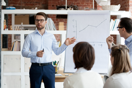 Serious confident business coach gives presentation on flipchart training workers group, executive presenter team leader explaining graph on whiteboard teach sales team employees at corporate meeting Foto de archivo - 116533575