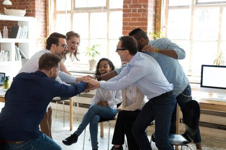 Gelukkige multi-etnische corporate teammedewerkers slaan de handen ineen tijdens groepsbijeenkomst, kantoormedewerkers vieren succes veelbelovende eenheid helpen ondersteuning bij teamwerk betrokken bij motiverende zakelijke training