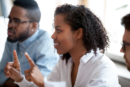 African american female worker student involved in team discussion brainstorm, black employee contribute opinion having idea offering solution at group meeting, participating in teambuilding training Фото со стока