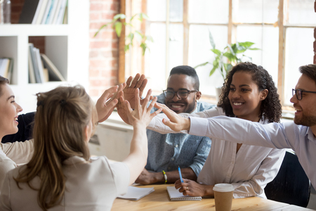 Happy african and caucasian diverse people give high five together celebrate great teamwork result motivated by team spirit, business success victory, unity concept, good relations and teambuilding Stockfoto - 116534155