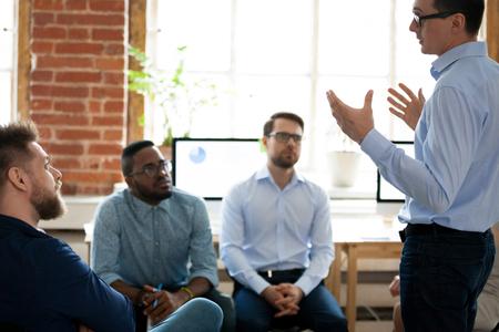 Entrenador mentor líder masculino confiado que habla en la reunión del equipo diverso, gerente del orador presentador que explica la nueva estrategia del plan de negocios al grupo de empleados durante la sesión informativa de la oficina en la capacitación corporativa