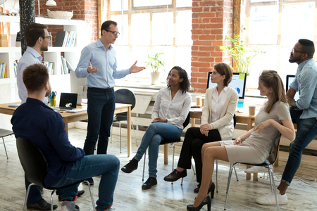 Diverse business team employees listening to male manager coach speaking at group office meeting, mentor executive leader talking during briefing, multi-ethnic workers engaged in corporate training