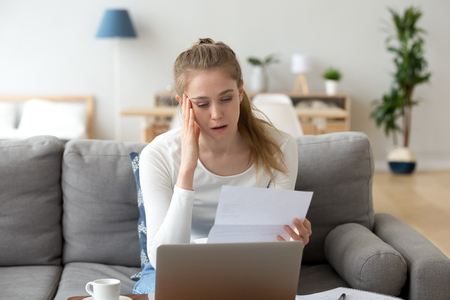 Upset frustrated girl reading bad news in paper letter feeling sad desperate about bank debt, unpaid bills, financial problem, stressed woman intern student unhappy received negative exam test result Stock Photo
