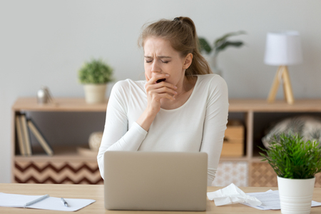 Joven mujer cansada y soñolienta bostezando trabajando o estudiando con una computadora portátil, estudiante aburrido y perezoso divertido que se siente privado de sueño después de una noche de insomnio de preparación para un examen aburrido, falta de sueño y concepto de aburrimiento