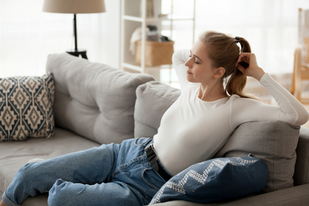 Relaxed young woman resting on comfortable couch relaxing breathing fresh air, happy lazy satisfied teenager girl stretching on sofa enjoying no stress free morning weekend pleasant day at home Stock Photo