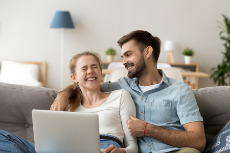 Happy young couple laughing at funny joke relaxing on couch with laptop, cheerful family enjoy weekend with device, joyful man and woman enjoying sincere laughter having fun with computer at home Stok Fotoğraf