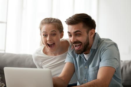 Emocionada pareja sorprendida mirando portátil feliz sorprendida por la oferta ganadora de apuestas en línea, buenas noticias de Internet, increíble oferta de venta por correo electrónico celebrar el logro de la victoria, sentirse ganadores, ver el juego