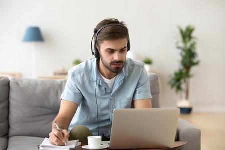 Hombre joven serio que mira la computadora portátil que usa los auriculares que aprenden el idioma extranjero, el conocimiento de la formación que escucha el seminario web que hace notas, el estudio en línea, el e-coaching, la educación a distancia, el concepto de e-learning Foto de archivo