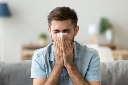 Joven enfermo estornudando con un pañuelo que sopla limpiando la nariz que moquea, un tipo alérgico enfermo que se resfrió tiene gripe, fiebre del heno, tos, que tiene síntomas de alergia estacional, enfermedad respiratoria contagiosa