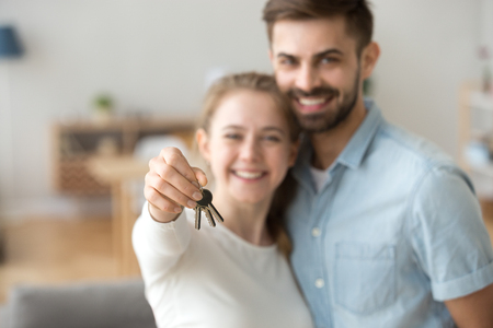 Happy young married family couple holding keys to new flat, excited home owners tenants looking at camera in own house, smiling customers buying estate modern apartment, property ownership concept