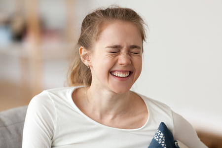 Happy young girl laughing, cheerful casual woman teenager with funny face expression enjoying sincere positive emotions, laughter concept, joyful cute teen making fun at humor joke chuckling