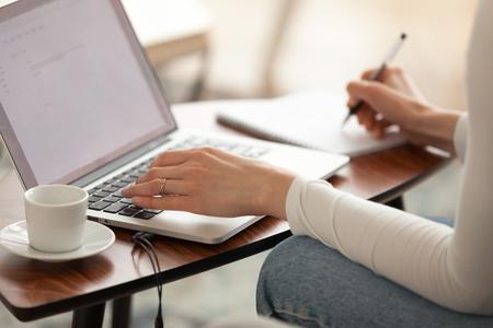 Une étudiante prenant des notes en étudiant l'apprentissage en ligne avec un ordinateur, une femme d'affaires rédactrice indépendante travaillant sur un ordinateur portable, des mains féminines écrivant un essai d'information à partir d'une vue rapprochée d'Internet Banque d'images