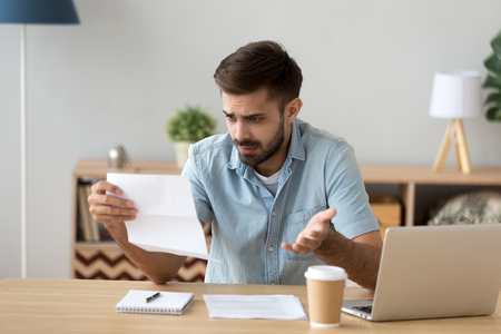 Confused frustrated young man holding mail letter reading shocking unexpected news nonsense in paper document, mad about high bill tax invoice, debt notification, bad financial report, money problem