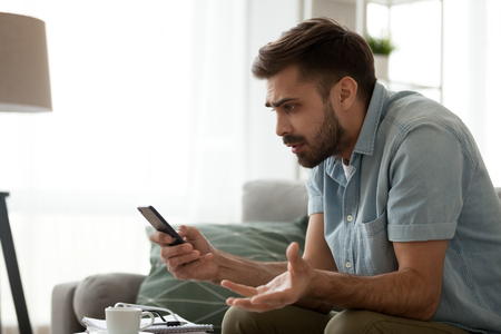 Angry confused man holding discharged phone annoyed by spam message, missed call or bad mobile signal looking at smartphone, mad male customer frustrated by cellphone problem receiving bad news Stock Photo - 116535034