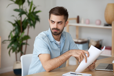 Serious thoughtful man looking away holding documents thinking of work problem solution, concerned pensive guy sitting at work desk doing paperwork, student or writer with paper lost in thoughts Stock Photo - 116535045
