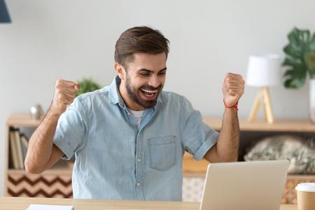 Euforyczny młody człowiek świętujący sukces zwycięstwa podekscytowany wygraną licytacją zakładu online w domu patrząc na laptopa, szczęśliwy zwycięzca płci męskiej czuje się szczęśliwy, że odniósł sukces, dostał nową możliwość pracy, otrzymał dobry wynik testu egzaminacyjnego