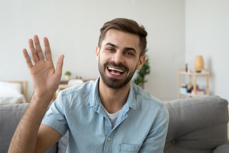 Friendly happy young man waving hand saying hello looking at camera greeting distant friend making online call, cheerful male vlogger blogger recording vlog teaching e-coaching via webcam, portrait Stok Fotoğraf