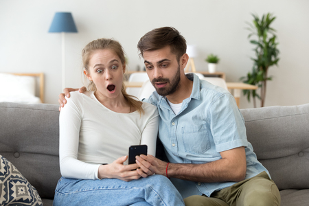 Astonished young couple surprised by unbelievable news in social media looking at mobile cell phone, shocked man and woman amazed or scared by internet content using online app on smartphone Foto de archivo